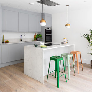 Inspiration for a contemporary galley kitchen in London with a submerged sink, flat-panel cabinets, grey cabinets, stainless steel appliances, light hardwood flooring, an island, beige floors and white worktops.