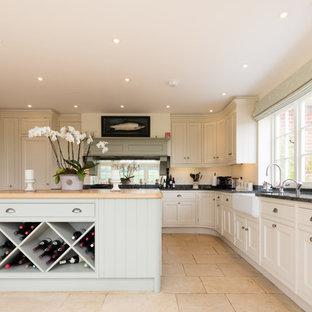 ウィルトシャーのトラディショナルスタイルのおしゃれなキッチン (エプロンフロントシンク、インセット扉のキャビネット、白いキャビネット、木材カウンター、ミラータイルのキッチンパネル、ベージュの床、ベージュのキッチンカウンター) の写真