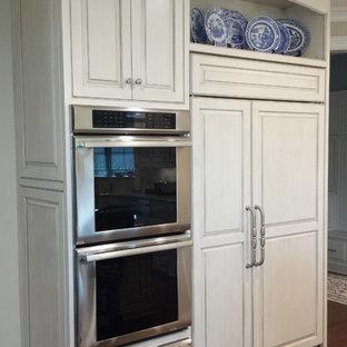 Ejemplo de cocina clásica con armarios con rebordes decorativos, puertas de armario blancas, encimera de granito, salpicadero de piedra caliza, suelo de madera en tonos medios, una isla, suelo marrón y electrodomésticos con paneles