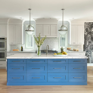 Design ideas for a large transitional eat-in kitchen in St Louis with an undermount sink, shaker cabinets, blue cabinets, solid surface benchtops, glass tile splashback, stainless steel appliances, light hardwood floors, with island and grey splashback.