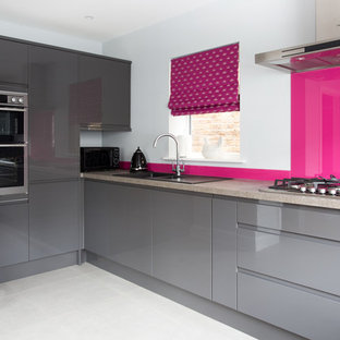 Mid-sized modern l-shaped open plan kitchen in Surrey with a drop-in sink, flat-panel cabinets, grey cabinets, granite benchtops, pink splashback, panelled appliances and porcelain floors.