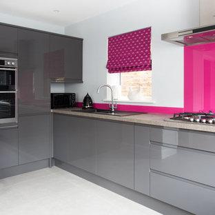 Modelo de cocina en L, minimalista, de tamaño medio, abierta, con fregadero encastrado, armarios con paneles lisos, puertas de armario grises, encimera de granito, salpicadero rosa, electrodomésticos con paneles y suelo de baldosas de porcelana