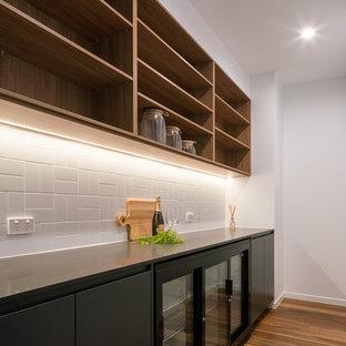 サンシャインコーストの中サイズのコンテンポラリースタイルのおしゃれなキッチン (黒いキャビネット、クオーツストーンカウンター、白いキッチンパネル、サブウェイタイルのキッチンパネル、黒い調理設備、無垢フローリング、アイランドなし、マルチカラーの床、黒いキッチンカウンター) の写真