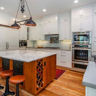 デンバーのエクレクティックスタイルのおしゃれなキッチン (エプロンフロントシンク、シェーカースタイル扉のキャビネット、白いキャビネット、コンクリートカウンター、白いキッチンパネル、ガラスタイルのキッチンパネル、パネルと同色の調理設備、淡色無垢フローリング、茶色い床、グレーのキッチンカウンター) の写真