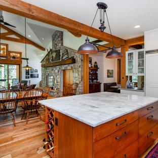 デンバーの中サイズのエクレクティックスタイルのおしゃれなキッチン (エプロンフロントシンク、シェーカースタイル扉のキャビネット、白いキャビネット、珪岩カウンター、白いキッチンパネル、ガラスタイルのキッチンパネル、パネルと同色の調理設備、淡色無垢フローリング、茶色い床、グレーのキッチンカウンター) の写真