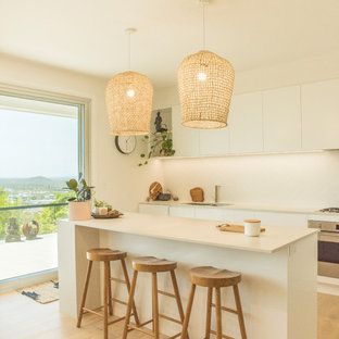 Design ideas for a large contemporary l-shaped open plan kitchen in Sunshine Coast with flat-panel cabinets, white cabinets, quartz benchtops, white splashback, ceramic splashback, light hardwood floors, with island and white benchtop.