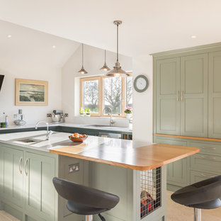 Inspiration for a beach style l-shaped kitchen in Other with a drop-in sink, shaker cabinets, green cabinets, white splashback, with island, beige floor and white benchtop.