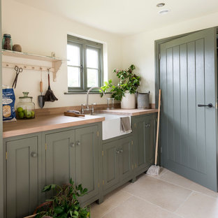 Inspiration for a country single-wall kitchen remodel in West Midlands with a farmhouse sink, shaker cabinets, green cabinets, wood countertops and stainless steel appliances