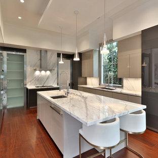 ロサンゼルスの大きいコンテンポラリースタイルのおしゃれなキッチン (ドロップインシンク、フラットパネル扉のキャビネット、グレーのキャビネット、大理石カウンター、白いキッチンパネル、大理石の床、パネルと同色の調理設備、無垢フローリング、茶色い床、白いキッチンカウンター) の写真