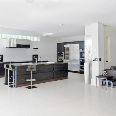 Example of a huge minimalist l-shaped gray floor open concept kitchen design with an undermount sink, flat-panel cabinets, dark wood cabinets, stainless steel appliances, an island and gray countertops