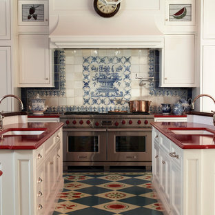 Farmhouse kitchen designs - Example of a cottage u-shaped multicolored floor kitchen design in New York with white cabinets, multicolored backsplash, an undermount sink, recessed-panel cabinets, stainless steel appliances, two islands and red countertops