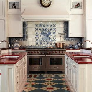 Cette image montre une cuisine rustique en U avec des portes de placard blanches, une crédence multicolore, un évier encastré, un placard avec porte à panneau encastré, un électroménager en acier inoxydable, 2 îlots, un sol multicolore et un plan de travail rouge.