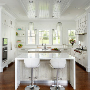 This is an example of a transitional kitchen in New York with flat-panel cabinets, recycled glass benchtops, multiple islands and white benchtop.