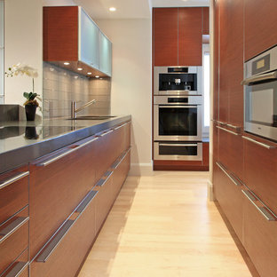 Design ideas for a contemporary kitchen in Boston with a triple-bowl sink, flat-panel cabinets, medium wood cabinets, concrete benchtops, stainless steel appliances, light hardwood floors and with island.