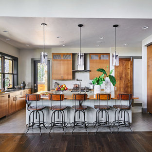 This is an example of a large tropical u-shaped open plan kitchen in Portland with flat-panel cabinets, dark wood cabinets, quartz benchtops, grey splashback, glass sheet splashback, panelled appliances, porcelain floors, with island and grey floor.