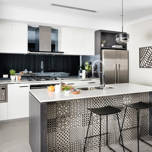 Small contemporary galley open plan kitchen in Perth with a double-bowl sink, flat-panel cabinets, white cabinets, black splashback, glass sheet splashback, stainless steel appliances and with island.