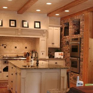 ルイビルの中くらいのカントリー風おしゃれなキッチン (白いキャビネット、ベージュキッチンパネル、シルバーの調理設備、無垢フローリング、アンダーカウンターシンク、シェーカースタイル扉のキャビネット、御影石カウンター、トラバーチンのキッチンパネル、茶色い床、茶色いキッチンカウンター) の写真
