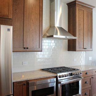 Exemple d'une petite cuisine américaine parallèle craftsman avec un évier 2 bacs, un placard à porte shaker, des portes de placard en bois brun, un plan de travail en quartz modifié, une crédence beige, une crédence en carrelage métro, un électroménager en acier inoxydable, un sol en bois brun et aucun îlot.