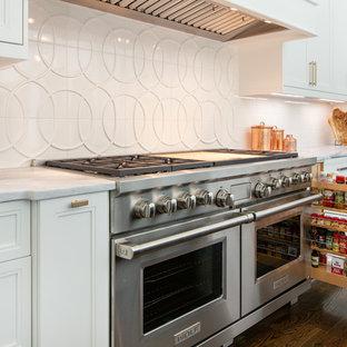 Bild på ett stort vintage vit vitt kök, med en dubbel diskho, luckor med profilerade fronter, vita skåp, bänkskiva i kvartsit, vitt stänkskydd, stänkskydd i keramik, integrerade vitvaror, mörkt trägolv och en köksö