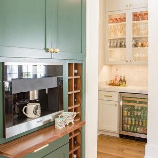 Diseño de cocina en U, tradicional renovada, grande, abierta, con armarios estilo shaker, puertas de armario verdes, encimera de cuarzo compacto, salpicadero blanco, electrodomésticos de acero inoxidable, suelo de madera clara y una isla