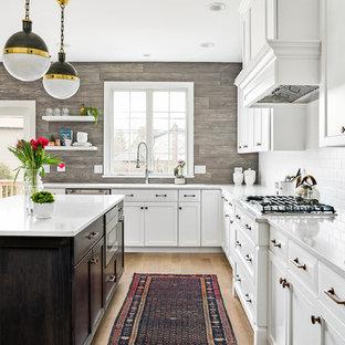 シカゴのカントリー風おしゃれなアイランドキッチン (アンダーカウンターシンク、落し込みパネル扉のキャビネット、白いキャビネット、白いキッチンパネル、サブウェイタイルのキッチンパネル、シルバーの調理設備、淡色無垢フローリング、ベージュの床、白いキッチンカウンター) の写真
