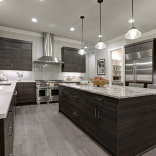 Large modern u-shaped separate kitchen in Chicago with flat-panel cabinets, dark wood cabinets, grey splashback, glass tile splashback, stainless steel appliances, medium hardwood floors, with island, grey floor and an undermount sink.