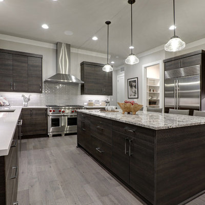 Example of a large minimalist u-shaped medium tone wood floor and gray floor enclosed kitchen design in Chicago with flat-panel cabinets, dark wood cabinets, gray backsplash, glass tile backsplash, stainless steel appliances, an island and an undermount sink