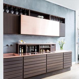 Modern inredning av ett litet linjärt kök med öppen planlösning, med en nedsänkt diskho, släta luckor, bruna skåp, bänkskiva i akrylsten och grått stänkskydd
