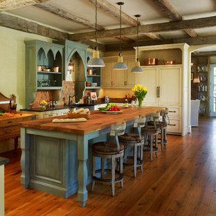 ワシントンD.C.の地中海スタイルのおしゃれなキッチン (エプロンフロントシンク、落し込みパネル扉のキャビネット、ヴィンテージ仕上げキャビネット、木材カウンター、パネルと同色の調理設備、濃色無垢フローリング) の写真