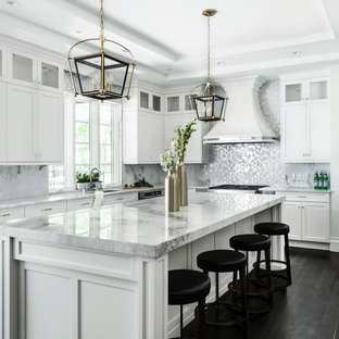 Design ideas for an expansive classic u-shaped kitchen/diner in New York with a submerged sink, shaker cabinets, white cabinets, quartz worktops, stainless steel appliances, dark hardwood flooring, an island and metallic splashback.