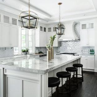 Foto på ett mycket stort vintage kök, med en undermonterad diskho, skåp i shakerstil, vita skåp, bänkskiva i kvartsit, rostfria vitvaror, mörkt trägolv, en köksö och stänkskydd med metallisk yta