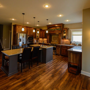 Large craftsman eat-in kitchen pictures - Eat-in kitchen - large craftsman u-shaped dark wood floor eat-in kitchen idea in Kansas City with an undermount sink, raised-panel cabinets, medium tone wood cabinets, quartz countertops, brown backsplash, ceramic backsplash, stainless steel appliances and an island