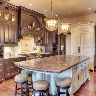 This is an example of a large traditional l-shaped eat-in kitchen in Kansas City with raised-panel cabinets, brown cabinets, tile benchtops, white splashback, ceramic splashback, stainless steel appliances and with island.
