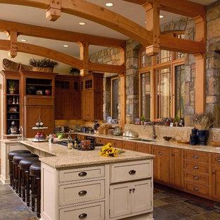 Ejemplo de cocina en L, rústica, con fregadero bajoencimera, armarios con paneles empotrados, puertas de armario de madera oscura, suelo de pizarra y una isla