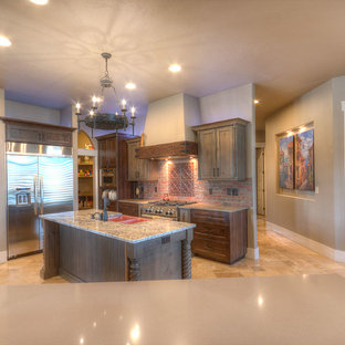 ボイシの中サイズのラスティックスタイルのおしゃれなキッチン (エプロンフロントシンク、シェーカースタイル扉のキャビネット、御影石カウンター、赤いキッチンパネル、レンガのキッチンパネル、シルバーの調理設備の、トラバーチンの床、ベージュの床、グレーのキャビネット、マルチカラーのキッチンカウンター) の写真