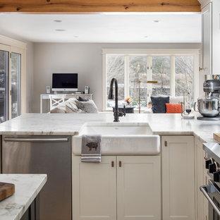 Große Klassische Küche in L-Form mit Landhausspüle, gelben Schränken, Marmor-Arbeitsplatte, Küchenrückwand in Weiß, Rückwand aus Marmor, Küchengeräten aus Edelstahl, hellem Holzboden, Kücheninsel, braunem Boden und weißer Arbeitsplatte in Boston