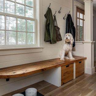 Inspiration för stora klassiska vitt l-kök, med en rustik diskho, gula skåp, marmorbänkskiva, vitt stänkskydd, stänkskydd i marmor, rostfria vitvaror, ljust trägolv, en köksö och brunt golv