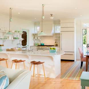 Idéer för ett lantligt kök, med vita skåp, vitt stänkskydd, integrerade vitvaror, ljust trägolv och en halv köksö