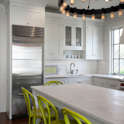 Inspiration for a transitional l-shaped eat-in kitchen remodel in Boston with an undermount sink, shaker cabinets, white cabinets, white backsplash and stainless steel appliances