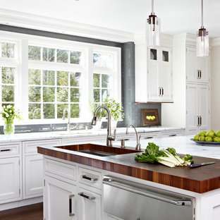 Traditional kitchen inspiration - Elegant kitchen photo in New York with an undermount sink, shaker cabinets, white cabinets, marble countertops, gray backsplash, subway tile backsplash, stainless steel appliances and an island