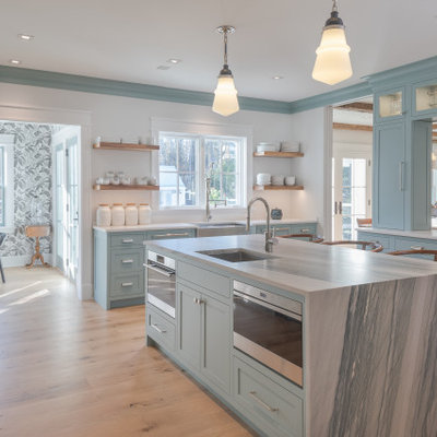 Eat-in kitchen - large country u-shaped light wood floor and beige floor eat-in kitchen idea in New York with a farmhouse sink, blue cabinets, marble countertops, white backsplash, marble backsplash, stainless steel appliances, an island, gray countertops and shaker cabinets