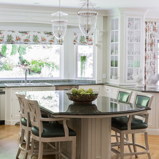Ejemplo de cocina comedor en L, clásica, de tamaño medio, con una isla, fregadero de tres senos, armarios con rebordes decorativos, puertas de armario blancas, encimera de granito, electrodomésticos de acero inoxidable, suelo de madera clara, salpicadero de vidrio, suelo beige y encimeras verdes