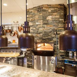 ボストンの広いトラディショナルスタイルのおしゃれなキッチン (フラットパネル扉のキャビネット、ステンレスキャビネット、御影石カウンター、グレーのキッチンパネル、石タイルのキッチンパネル、シルバーの調理設備) の写真