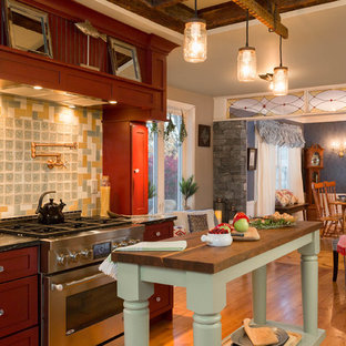 Photo of a large traditional u-shaped eat-in kitchen in Boston with a single-bowl sink, shaker cabinets, green cabinets, granite benchtops, multi-coloured splashback, glass tile splashback, panelled appliances, medium hardwood floors and multiple islands.
