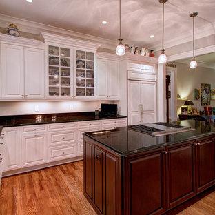 Große Klassische Wohnküche in L-Form mit Unterbauwaschbecken, Schrankfronten mit vertiefter Füllung, weißen Schränken, Onyx-Arbeitsplatte, Küchengeräten aus Edelstahl, braunem Holzboden und Kücheninsel in Charlotte