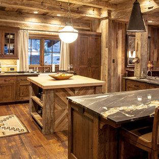 Modelo de cocina rural, grande, con fregadero sobremueble, armarios tipo vitrina, puertas de armario de madera en tonos medios, salpicadero de madera, suelo de madera oscura y una isla