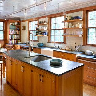 Classic galley kitchen/diner in New York with a belfast sink, medium wood cabinets, white splashback, metro tiled splashback, an island, beige floors and grey worktops.