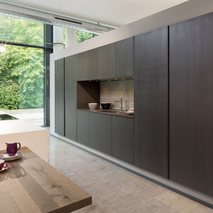 Photo of a large contemporary single-wall open plan kitchen in Oxfordshire with an undermount sink, flat-panel cabinets, black cabinets, quartz benchtops, metallic splashback, glass tile splashback, black appliances, cement tiles and with island.