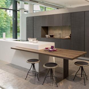 Immagine di una grande cucina contemporanea con lavello sottopiano, ante lisce, ante beige, top in quarzo composito, paraspruzzi a effetto metallico, paraspruzzi con piastrelle di vetro, elettrodomestici neri, pavimento con cementine e isola