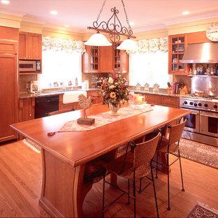 ニューヨークの大きいビーチスタイルのおしゃれなキッチン (エプロンフロントシンク、落し込みパネル扉のキャビネット、中間色木目調キャビネット、御影石カウンター、メタリックのキッチンパネル、メタルタイルのキッチンパネル、シルバーの調理設備の、淡色無垢フローリング、茶色い床) の写真